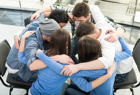 terapia de grupo: Círculo de la confianza. Grupo de personas que están sentadas abrazando en círculo y se apoyan mutuamente. Foto de archivo