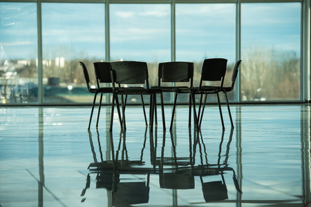Several chairs stand in a circle on the background panoramic windows. The meeting place for support groups. photo