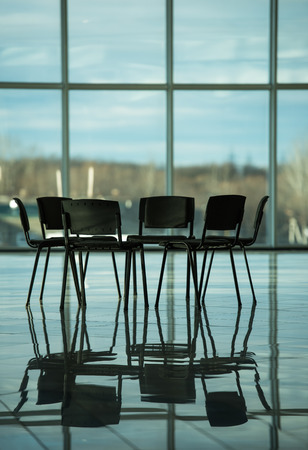 meeting place: Several chairs stand in a circle on the background panoramic windows. The meeting place for support groups. Stock Photo
