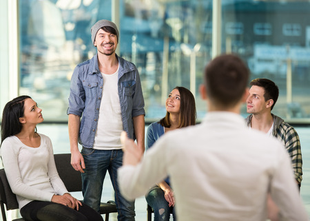 Young man is sharing his problems with people. View of man is telling something and gesturing while group of people are sitting in front of him and listening. photo