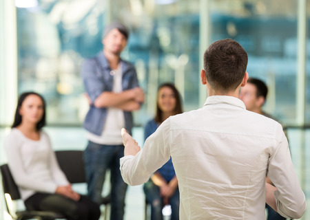 terapia de grupo: Hombre joven está compartiendo sus problemas con la gente. Vista del hombre está diciendo algo y gesticulando mientras que el grupo de personas que están sentados frente a él y escuchar.