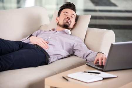 tired businessman: Tired businessman is sleeping on the sofa at the office. Stock Photo