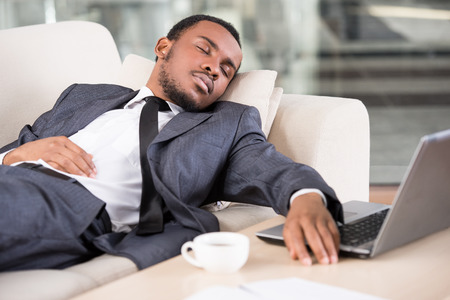 sleeping at desk: Young African business man is holding hand on laptop keyboard while sleeping on the couch. Stock Photo