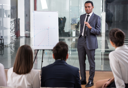 Image of several business people are looking at successful specialist is explaining new project at board. Stock Photo