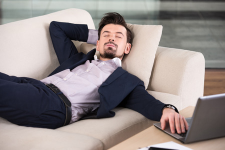 Tired businessman is sleeping on the sofa at the office. photo