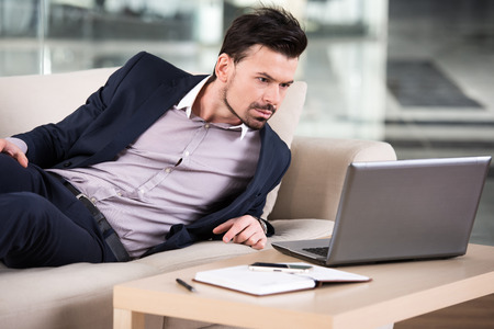 Businessman is looking at his laptop while lying on the couch in the office. photo
