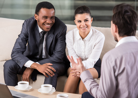 coffee table: Group of smiling business partners are interacting in office during coffee break.
