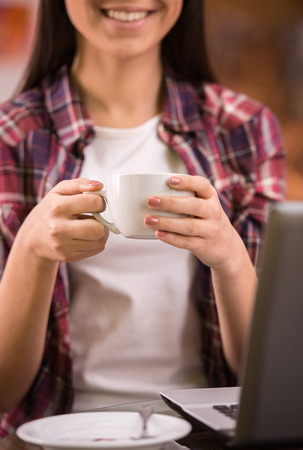 Happy young woman is drinking coffee and using laptop in a coffee shop. photo