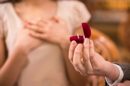 proposal of marriage: Young man is presenting engagement ring to his girlfriend.