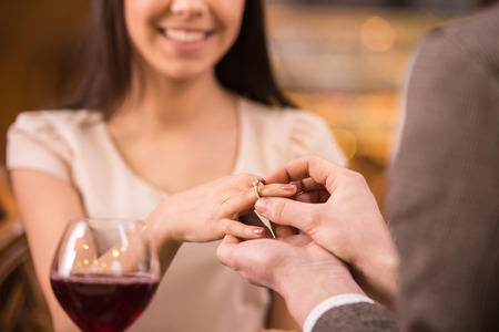 A man is giving a ring as a gift to a female in an outdoor cafe.