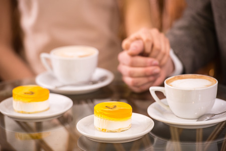 Romantic date in cafe. Coffee and cake on focus. photo
