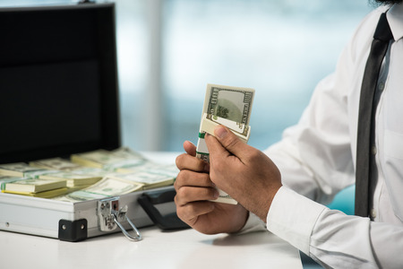 Close-up hands of businessman with suitcase full of money. photo