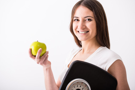 grey scale: Young happy woman is holding a weight scale and apple on grey . Stock Photo