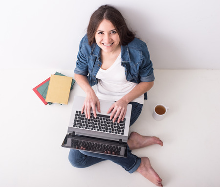 Top view of young woman is sitting on the floor with laptop, a cup of tea and books.  photo