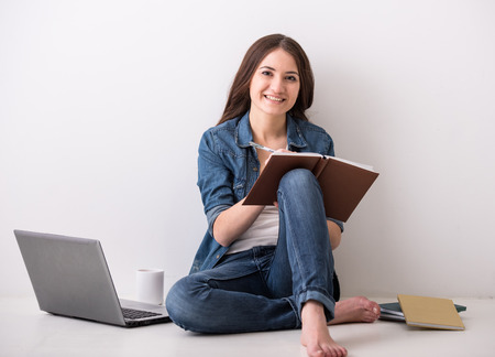 Young woman is sitting on the floor with laptop, a cup of tea and books. Grey background. photo