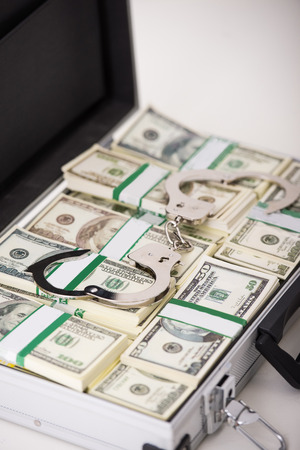 Close-up suitcase full of money and handcuffs. photo