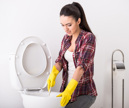 Woman with rubber glove is cleaning toilet bowl using brush. photo
