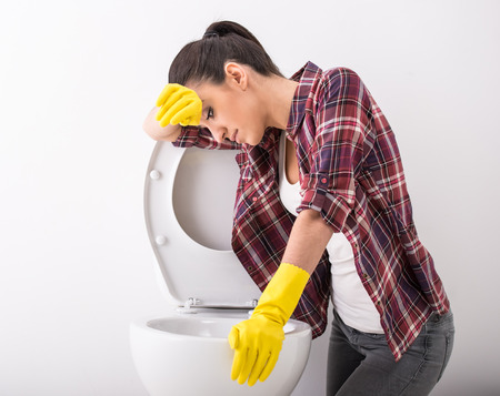 Exhausted young woman is cleaning a toilet on grey background. photo