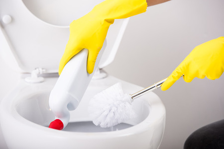 Female hand in yellow rubber glove is cleaning toilet bowl using brush.