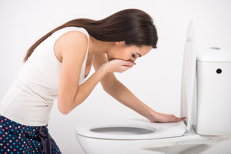Young woman vomiting into the toilet bowl in the early stages of pregnancy or after a night of partying and drinking. photo