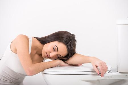 enfermos: Mujer joven dormida en el inodoro.