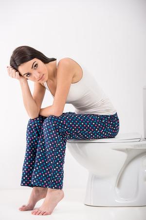 wc: Junge Frau sitzt in einer Toilette und in die Kamera.