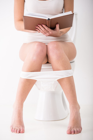 Close-up of woman on toilet with book in morning. photo