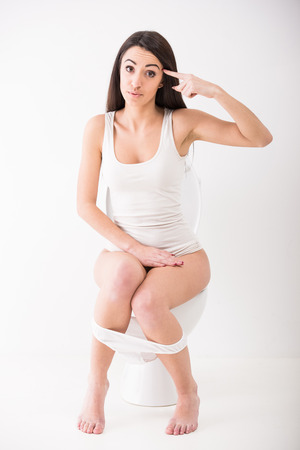 Young woman seated on toilet in morning. photo