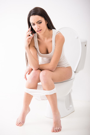 Young woman is talking by phone while seated on toilet in morning.