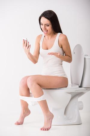 asiento: Mujer joven est� hablando por tel�fono mientras se est� sentado en el inodoro en la ma�ana.