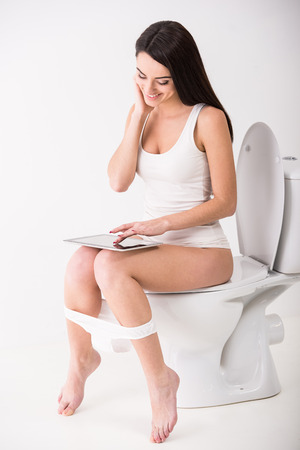 Young woman is using tablet while seated on toilet in morning.