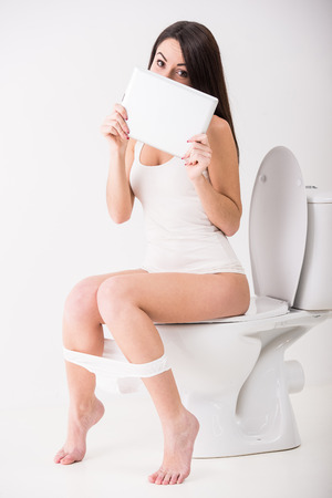 peeing: Young woman is using tablet while seated on toilet in morning.