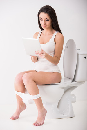 business woman legs: Young woman is using tablet while seated on toilet in morning.