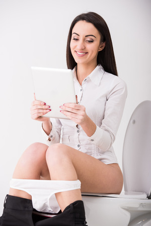 peeing: Young businesswoman is using tablet while seated on toilet in morning.