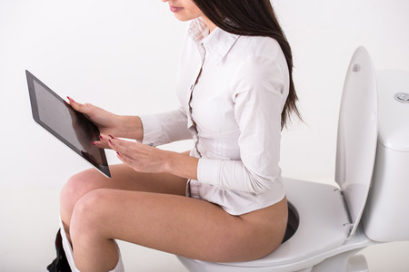 Young businesswoman is using tablet while seated on toilet in morning.