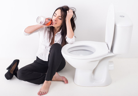 Young woman in depression, is drinking alcohol in toilet.
