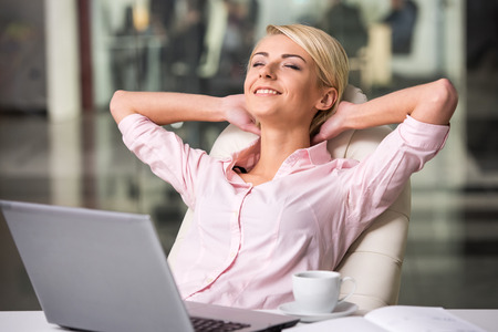 Mooie jonge zakenvrouw ontspannen op kantoor.
