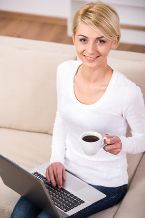 Young businesswoman is working with laptop at office and drinking coffee. photo