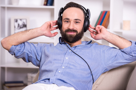 Young man is relaxing at home, listening to music using headphone. photo