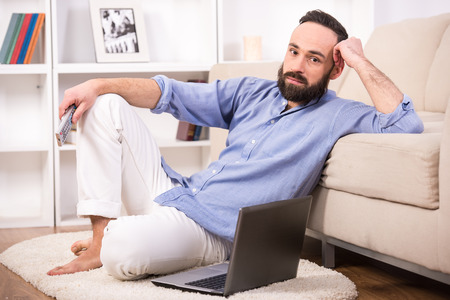 Attractive young man is sitting down at home living room, using a control remote while looking at the camera. photo