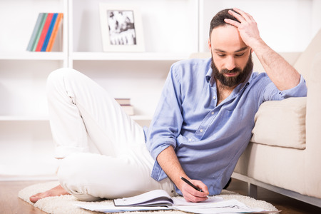 Man is sitting on the floor at home and working with documents. photo