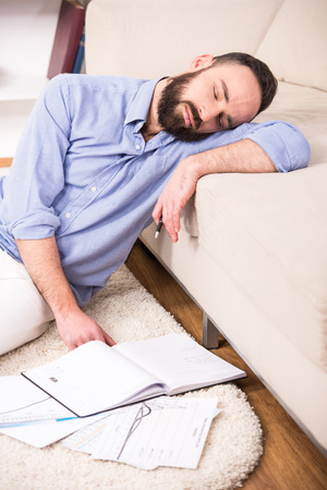 Man is sleeping while sitting on the floor at home with documents. photo