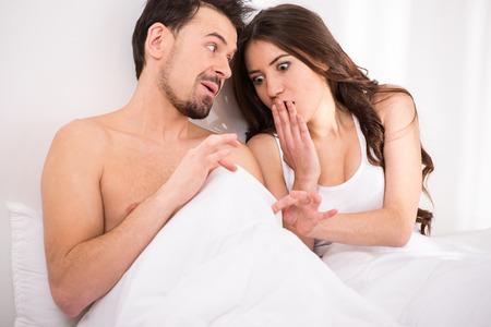 pene: Mujer joven sorprendida y sorprendido en la cama está mirando hacia abajo en el pene bajo blanco cubre la hoja en el dormitorio.