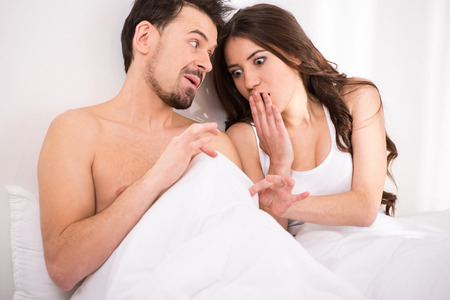 Surprised and shocked young woman in bed is looking down at penis under white covers sheet in bedroom. Stock Photo