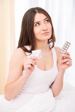 condones: Mujer joven es la elecci�n de su camino - cond�n o pastillas. Foto de archivo