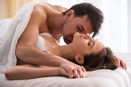 negativity: Young love couple in bed, romantic scene in bedroom.