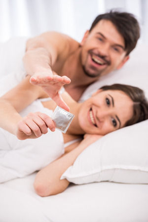 Smiling young couple in bed with condom are looking at the camera. photo