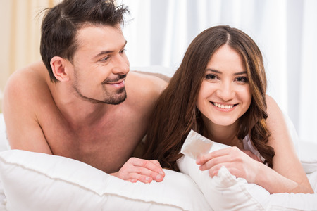 condones: Atractiva pareja joven en la cama con un condón.
