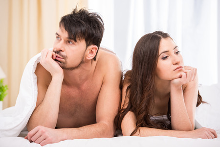 safe sex: Young couple under the covers in bed turned away from each other.