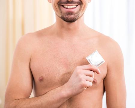 condones: Hombre atractivo joven que sostiene condón en la mano Foto de archivo